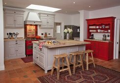 Wooden bar stools at free-standing island counter in open-plan, country-house kitchen in shades of pale grey and red with recessed spotlights in suspended ceiling