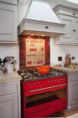 Pale grey, country-house-style fitted kitchen with red gas cooker under extractor hood
