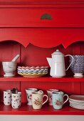 Plates and mugs on red-painted, country-house-style dresser