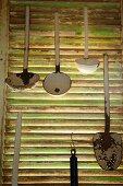 Various ladles hanging from slatted shutter