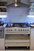 Gas cooker below stainless steel extractor hood integrated into kitchen counter
