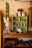 Angel figurine and small shelving unit painted green holding collection of funnels on wooden table