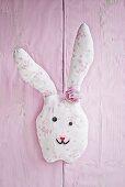 Hand-sewn fabric rabbit on pink wall