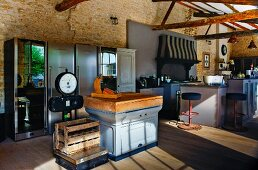 Old, country-house-style kitchen counter next to wooden crate on industrial scales; stainless steel fridges in background