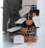 Stapel von schwarz-weiß eingepackten Geschenken mit kupferfarbenen Akzenten und Namensschildern