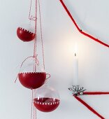 Glass baubles partly dipped in red paint and decorated with pattern of crosses next to lit candle