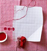 Sheet of white paper, hankd of thread and red paint on red and white gingham fabric