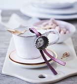 Place tag made from vintage photo stuck inside bottle cap on ribbon draped over teacup