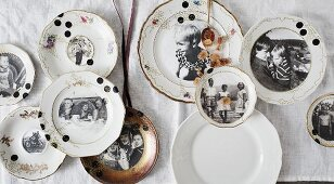 Vintage family photos on old gold-rimmed plates decorating wall