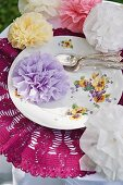 Romantic flowers made from folded serviettes on floral plate with silver cutlery