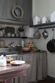 Many shelves of vintage storage jars and linen curtain on sink base unit in Mediterranean kitchen