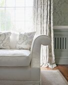 Armrest of classic sofa in front of lattice window with curtain and ornately patterned wallpaper