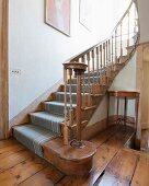 Antike Treppe aus Holz mit Teppich und gedrechseltem Geländer, alter Dielenboden