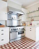 Geräumige Küche mit Profi-Herd und rot-weißem Schachbrettboden