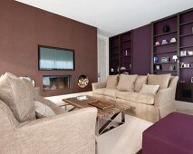 Fitted shelving, two sofas and fireplace in living room in warm shades