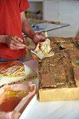 Hands of person applying gold leaf to artwork in artist's workshop