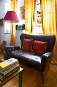 Floor-length, yellow curtains behind elegant, retro leather sofa and red standard lamp