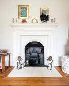 Open fireplace with white-painted surround and mantelpiece