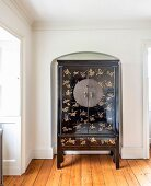 Black-lacquered Chinese wedding cabinet with gold inlays in arched niche