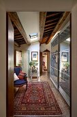 Antique armchair, Oriental rug and modern cupboards with sliding doors in foyer leading to long, narrow corridor
