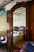 Antique wardrobe with mirrored door in traditional bedroom