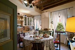 Round table with tablecloth in Mediterranean kitchen-dining room with gathered, white curtains on windows