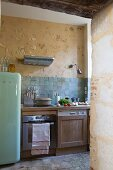 Retro fridge and kitchen counter with wooden cabinets in rustic kitchen