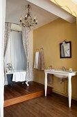 Nostalgisches Badezimmer mit gelben Wänden, Holzboden, Waschtisch und freistehender Badewanne auf Podest