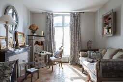 Marble fireplace, antique bureau and sofa in pale grey interior