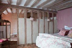 Schlafbereich in ländlichem Wohnraum mit Holzbalkendecke und Balkenwand