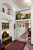 Antique wooden bench in illuminated niche and rug on tiled floor in hallway with furnished gallery