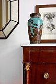 Painted, antique vase on cabinet in front of framed drawing leaning against wall