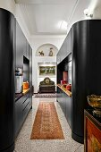 Modern, black cupboard installations with rounded edges in open-plan kitchen in traditional interior