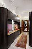 Contemporary, black cupboard installation in open-plan kitchen in traditional interior