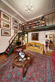 Antique, round coffee table on patterned rug in open-plan interior with staircase and gallery in traditional interior