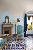 Elegant, ornate floor tiles and chairs with light blue upholstery in front of open fireplace (Villa Cimbrone Hotel)
