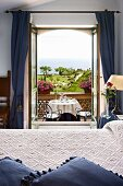 Hotel room with view of set table, park and ocean through open balcony doors (Villa Cimbrone Hotel, Italy)