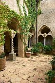 Courtyard with potted plants on terracotta floor and climber-covered arcades at Villa Cimbrone in Italy