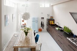 Long counter and rustic wooden table in kitchen with retro fridge in background
