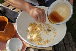 Mixing milk, marigold petals and honey for hand soak or scrub