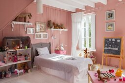 Pink walls, large dolls' house and bed with valance in vintage-style bedroom