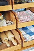 Kitchen utensils (tea towels, rolling pins) in wooden drawers