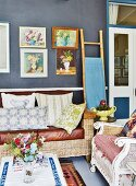 Vintage seating, gallery of pictures on wall and bamboo ladder in living room