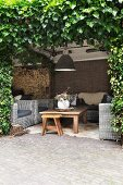 Stool, wicker armchairs and wooden coffee table below pendant lamp on secluded terrace