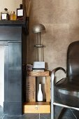 Vintage table lamp on shelf made from wooden crate next to armchair