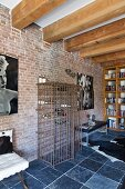 Wood-beamed ceiling, slate floor and metal-cage wine rack against brick wall in loft apartment