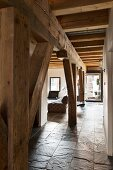 Rustic wooden supporting structure and ceiling beams in loft apartment with slate floor