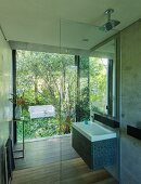 Designer bathroom with walk-in shower and view of white outdoor sofa in garden through glass wall