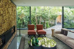Designer sofa, chaise armchairs and mirrored coffee table in front of fireplace in wall decorated with slices of tree trunk