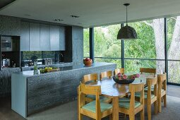 Oak dining set in front of kitchen with wooden cabinets in modern interior with glass wall